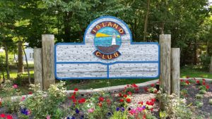 The entrance to the Island Club, greeted by its wooden sign.